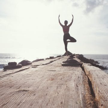 Woman posed for yoga at end of dock Financial Strategies Group blog