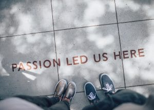"""Two young people in sneakers standing above writing on the sidewalk that reads, """"Passion led us here."""""""